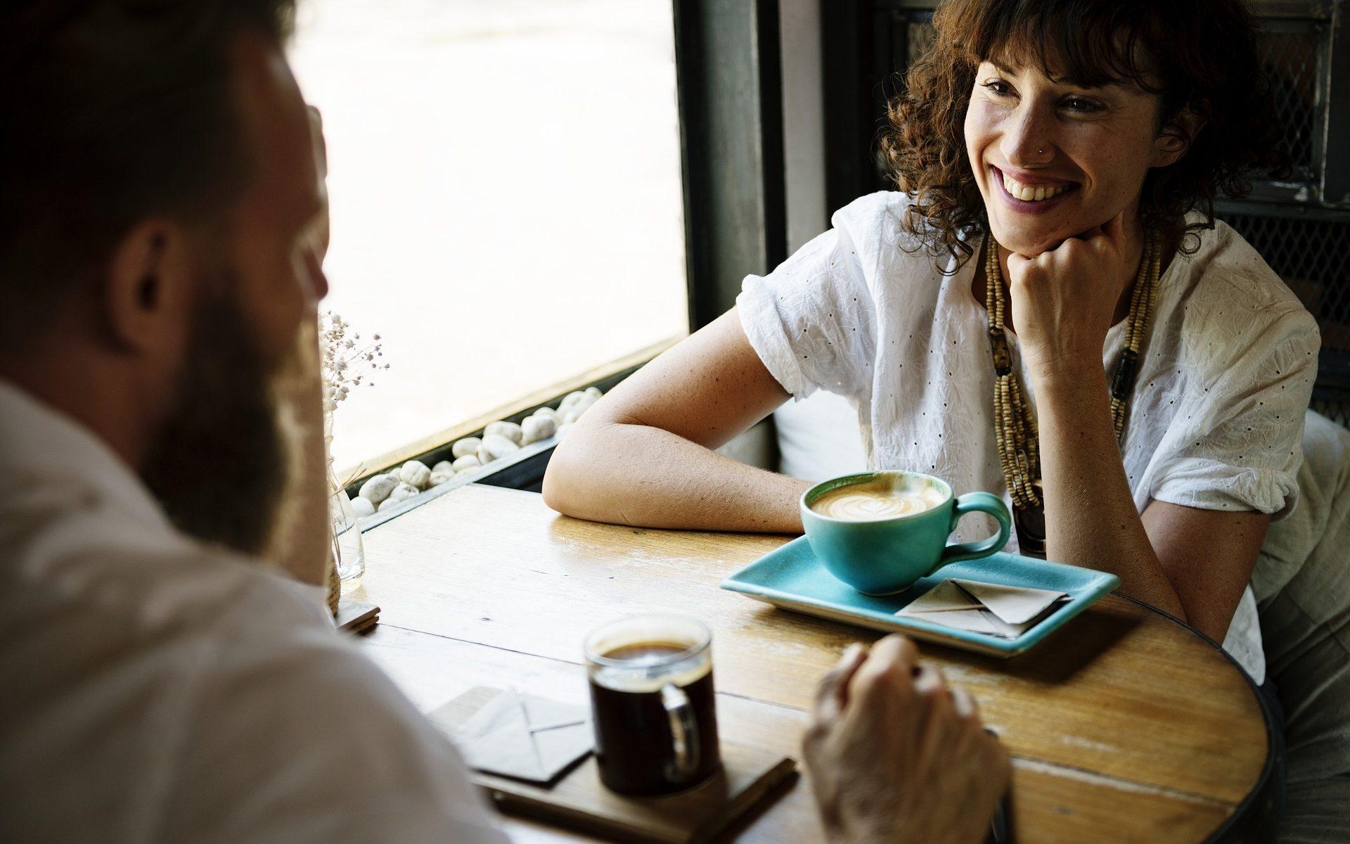 Mann und Frau flirten beim Kaffee trinken